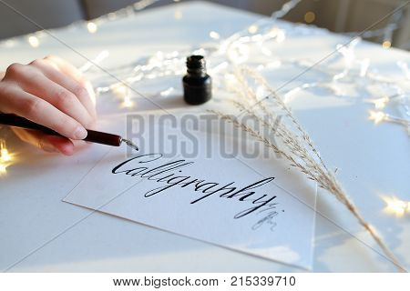 Girl calligrapher holds in hand wooden rod with pen for writing and dunks in black ink for writing beautiful letters and words for postcards, sits at white table with garland in art studio. Young woman of European appearance dressed in brown sweatshirt wi
