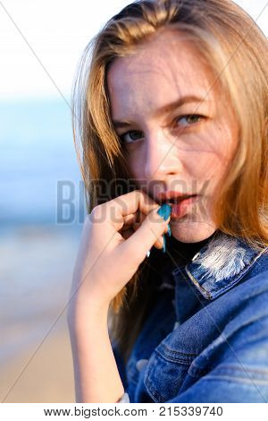 Beautiful girl with smile on lips plays with hair and shoots eyes, looks straight ahead and laughs coquettishly, developing hair in wind with eyes closed with pleasure. Young European-looking woman with blond mid-length hair dressed in blue denim jacket a