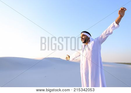 Handsome young Emirate strolls and stretches, spreads hands to sides and rests from city bustle, examines surroundings of wide desert with white sand.