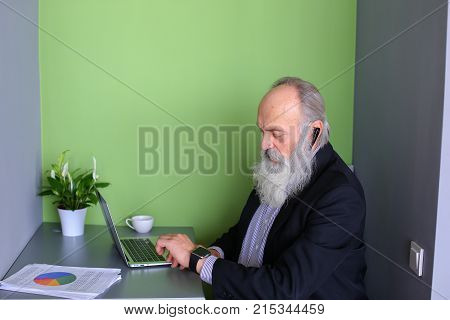Oldie modern men study new and modern technologies, learn to work with bluetooth headsets and iWatch, sitting and working on laptop in cozy computer cafe on sunny day. elderly man with long gray beard of European appearance dressed in black classic suit