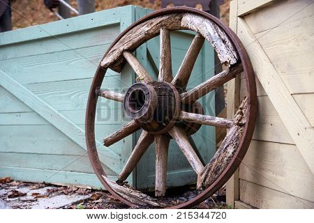 Old wood wagon wheel with spokes laying on boxes