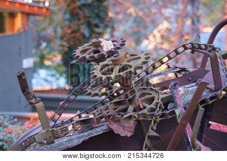 Large old metal gears rusting in leaves