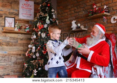 Santa Claus, sitting on armchair, holds small male child lap, cute boys head sweetly and gives long-awaited surprise in box. kid with pleasure impatience shakes coveted gift runs to unpack present. attractive European-looking boy dressed warm sweater