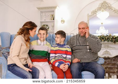 Friendly family of parents and children, two boys together was going to chat in room with fireplace. Woman communicates with mother-in-law on cell phone and hands husband to congratulate relatives on winter coming holidays
