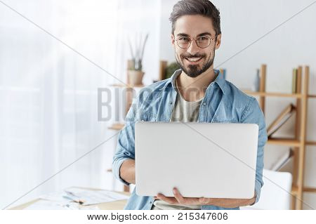 Handsome Cheerful Bearded Young Male Copywriter Types Information For Advertisment Of Website, Wears