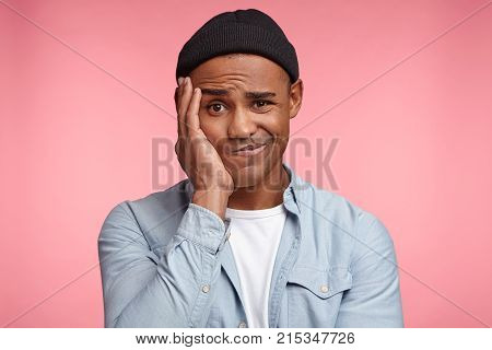 People, Youth, Style, Facial Expressions Concept. Hesitant Sunburnt Male In Trendy Hat And Shirt Fro