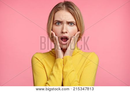 Scared Lovely Woman Looks With Terrible Expression, Being Surprised To Read Shocking News In Newspap