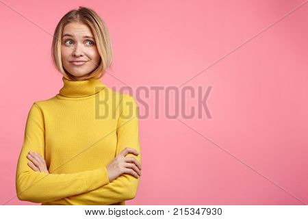 Young Woman Wears Casual Yellow Turtleneck Sweater, Keeps Hands Crossed, Looks With Hesitation Aside