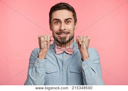 Hopeful Male Raises Fists In Anticipation, Has Wishful Expression, Hopes For Fortune And Good Luck,