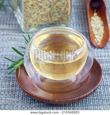 Herbal rosemary tea in glass cup on oriental background square format