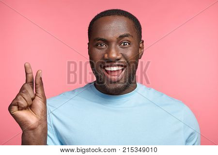 Cheerful Dark Skinned Male With Happy Expression Shows Something Tiny, Opens Mouth Widely, Shows Whi
