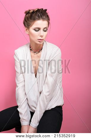 A delicate portrait in pink. Beautiful young woman in a light blouse on a pink background. Beads or decoration on the neck. Hairstyle and professional makeup. Gentle way slightly drooping head the model looks down