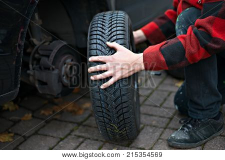 man in chequered jacket changing tyre on his car