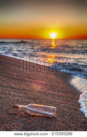 Bottle with message inside on the shore at the beach