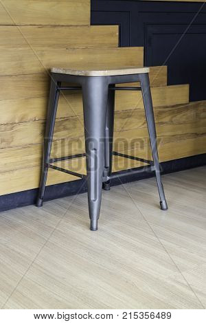 Wood and black metal bar chair on wall background stock photo