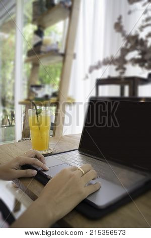 Woman with laptop and orange juice at table stock photo