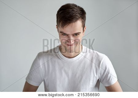 portrait of young Caucasian men dressed in white t-shirt with a devilish happy with the look askance came up with a cunning plan and you're satisfied.