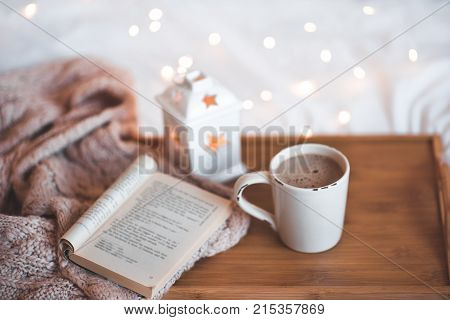 Good morning. Cup of coffee ith opn boon on wooden tray closeup over Christmas lights.
