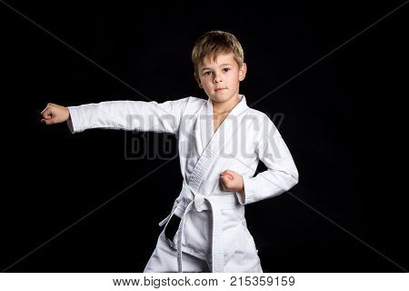 Straight karate arm hit. Kid in brand new kimono looking on the camera on isolated black background.