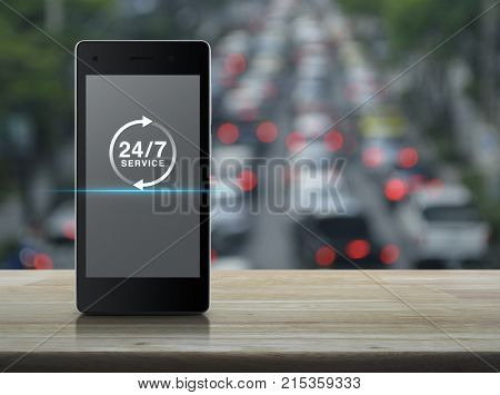 24 hours service icon on modern smart phone screen on wooden table over blur of rush hour with cars and road Full time service concept