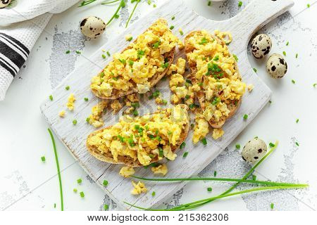 Homemade Quail Scrambled eggs on crispy toast, bread with green onion, chives on white board