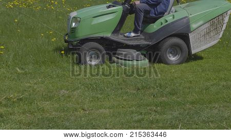 Worker mows green grass lawnmower on spring day
