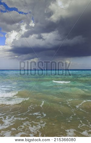 Apulia seascape: mediterranean sea,Italy. Summer thunderstorm on the horizon.  Rough sea with the sailing boat in the distance on the horizon dominated by thunderclouds.