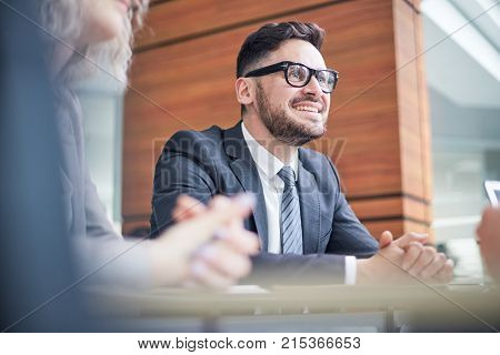 Portrait shot of cheerful bearded white collar worker listening to his colleague with interest while having working meeting at modern boardroom