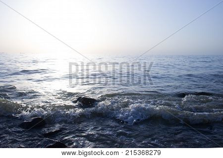 View of dawn at the seaside with the clear sky. surf waves and large boulder stones. Blue background with copy space.