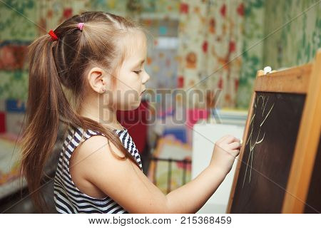 Girl with ponytail hairstyle in process of drawing picture of sun, kid creating new image with all carefulness on blackboard with chalk of green color, lady in dress
