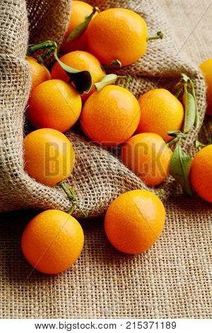 Kumquats or cumquats and shadow in sack bag on sack floor