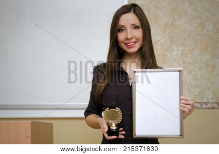 Best teacher. Best student. Graduate mock up . Award ceremony. Young teacher or student holds a gold medal and an empty photo frame with blank paper sheet with copy space on school board background.