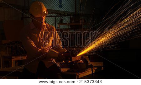 the man worker uses grinding cutting machine to cut metal focus on flash light line of sharp sparkin low Light