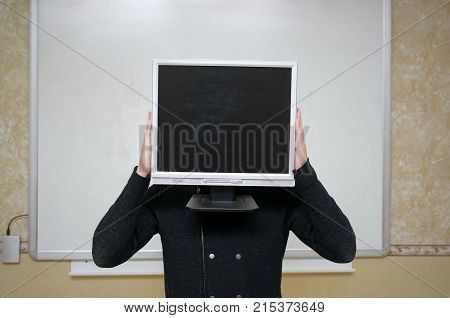 Education project presentation. Teacher or student hides his face behind computer monitor with blank screen on school board background with copy space. Education concept. Conspiracy. Education robot.