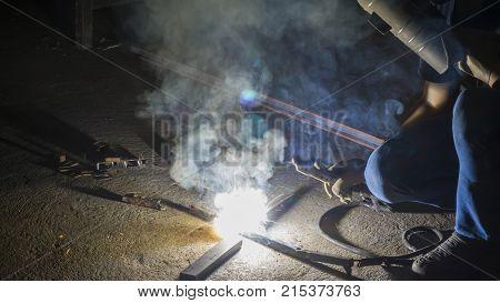 worker welding metal focus on flash light line of sharp sparkin low light