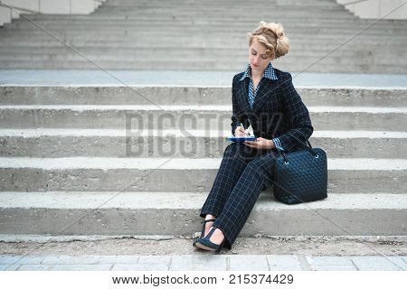 Horizontal shot of a young woman sitting on stairs with the notepad. Business concept