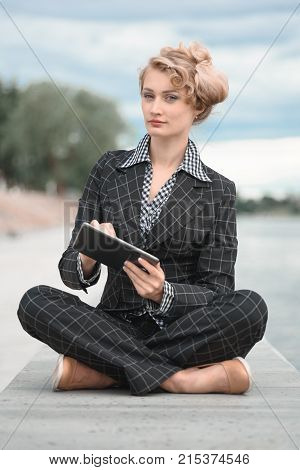 Vertical shot of a young woman sitting on promenade with the tablet and thinks. Business concept