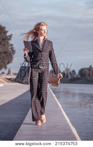 Vertical orange tonted shot of a beautiful blond woman walking with paper bags bag and tablet along the promenade
