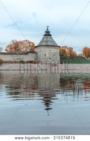 Vertical shot of tower and fortress wall reflecting in the river. Autumn landscape.