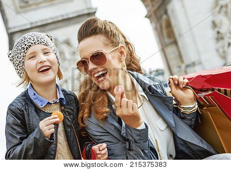 Stylish autumn in Paris. smiling trendy mother and daughter with shopping bags near Arc de Triomphe in Paris France eating macaroons