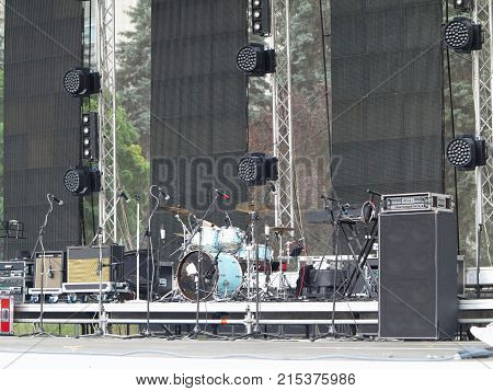 lighting equipment drums electronics and sound amplifiers on concert stage.