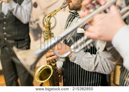 men from jazz band dressed in marvelous black costumes with thin white strips are playing sax of golden colour and silver trumpet