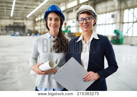 Cheerful beautiful female investor meeting with ambitious young architect at construction site and looking with confidence at camera