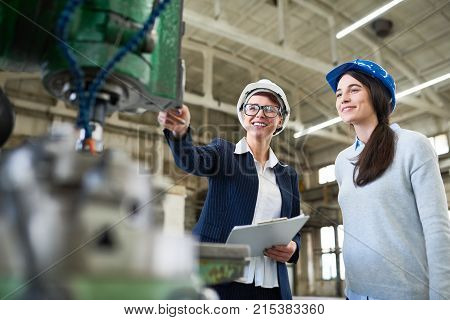 Cheerful lady boss presenting factory machine to inspector and sharing information about quality and maintenance in workshop