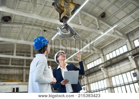 Cheerful female investor in hardhat pointing at construction crane and discussing building with forewoman at construction site