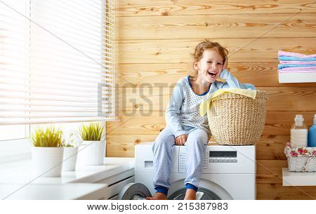 happy little funny housewife baby girl in laundry with washing machine