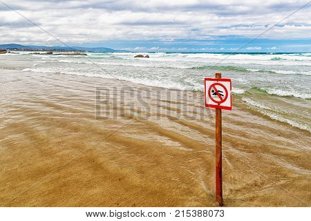 The sign forbidding to bathe on the beach. The sandy beach the sign on a wooden column is thrust in sand in the leaving wave. Appears through sand a horizontal shot water
