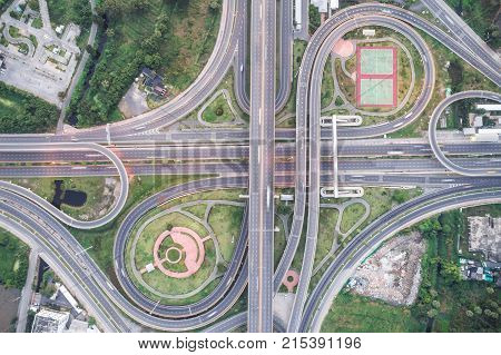 Aerial view of urbal highway intersection road with green exercise background in the morning light