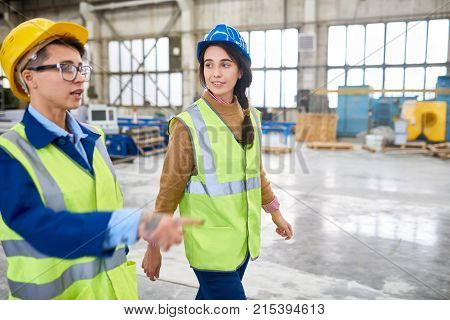 Confident experienced forewoman walking with female colleague over factory workshop and explaining her work