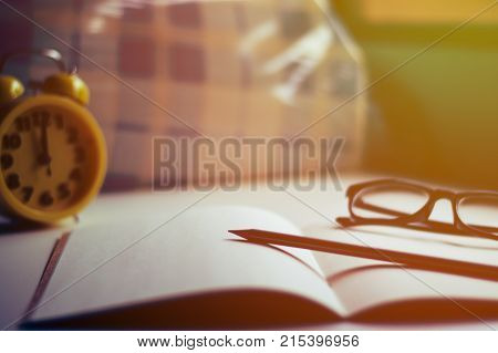 Notebook with clock, glasses and pencil on white table selective focus vintage style.
